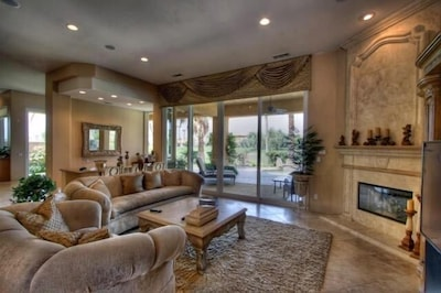 Living Room with large Sunken Bar and view of the pool and golf course.