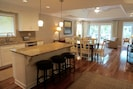 The renovated kitchen has a large island with 3 bar stools.