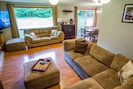 Living Room: Large sectional couches, wood fireplace, flatscreen TV with Netflix