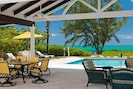 Covered porch for alfresco dining and relaxing at poolside