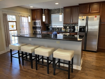 Fully equipped kitchen with bar seating, granite counters and hardwood floor.