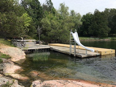 Floating dock,  slide, large deck with bench seating, table andoutdoor fire ring