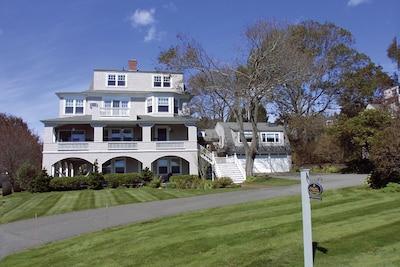 Front of SNI Cottage, showing various verandas, oceanview windows, lawn.