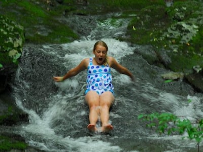 Cool off in Paul's Creek natural rock slide down in the valley.