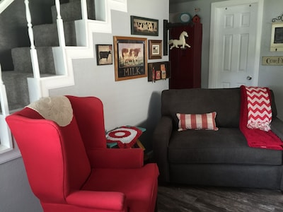 Open living room, view from the front door. Has a twin size sleeper and TV.