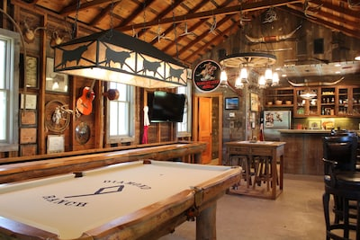 Saloon with custom pool table, shuffle board, game table, small kitchen.