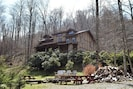 Cabin with huge fire pit area with picnic table with view of pond and mountain
