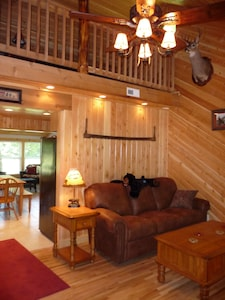 The living room of the cabin, with a view into the loft.
