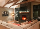 Warm, inviting great room with rustic beams, vaulted ceiling and large sectional
