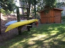 Shed with games and water toys behind kayak rack