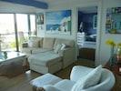 Greek villa lounge room, floor to ceiling glass overlooking the ocean