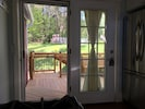 View from kitchen out to cedar deck to chicken coop (backyard)