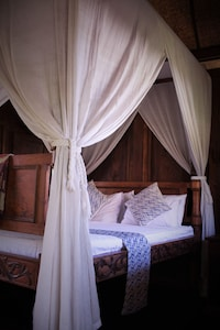Large bed in an antique four poster bed frame