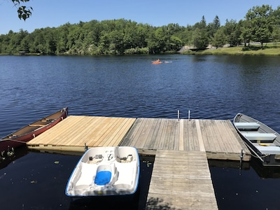 Private dock with canoe, rowboat, and a pedal boat.