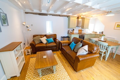 Open plan lounge area in cosy Colby Cottage.
