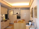 Open kitchen with oven, wash machine, micro wave and electrical cooker