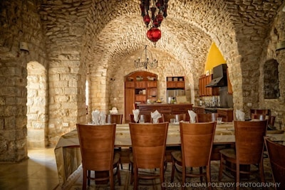 Elegant dining below a high stone dome. The table extends to seat 16 guests.