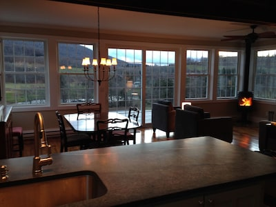 View from kitchen of open floor plan with wall of windows facing mountain views.