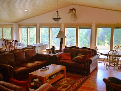 Living/dining area has 3 large tables with 5 couches to enjoy beautiful view