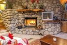 Beautiful river rock fireplace to warm your toes.
