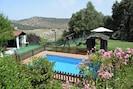 Piscina con amplia zona de césped natural integrada en los jardínes