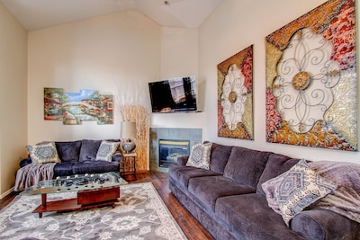 """Main level living room with fireplace and 60"""" TV"""