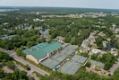 Aerial view of tennis center (green building) with 30+ har tru & hard courts