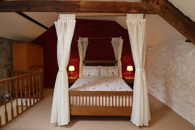 ... with a very comfy four-poster bed, original beams and stone walls.
