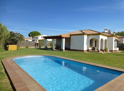 Villa with view of private pool and wrap around garden.