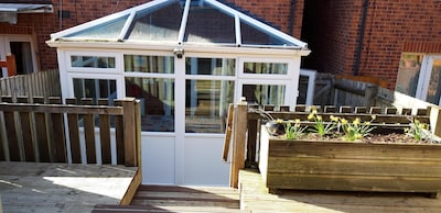 Rear garden decked area with rotary clothes line and access to rear parking