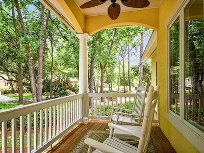 Large covered front porch with 4 rocking chairs and side tables for relaxing