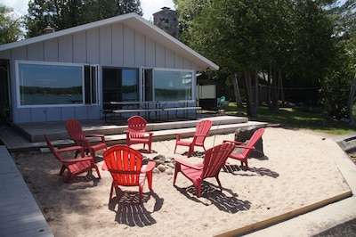 The Lake House with sandy frontage and a fire pit.