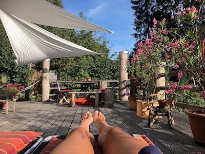 Grosszügige Terrasse mit Liegestühlen und Essgelegenheit  im Garten