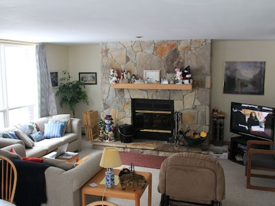 Relax on the sofa with fireplace, TV and picture  window looking at Season Pass