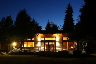 Main living space from yard at night.