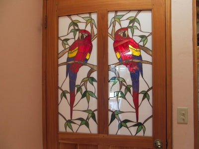 Inside entrance Teak door with stained glass scarlet Macaws by local artist