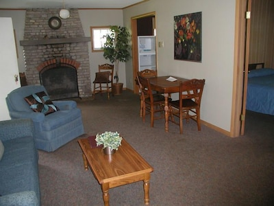 The living room has a working fireplace and a large bay window.