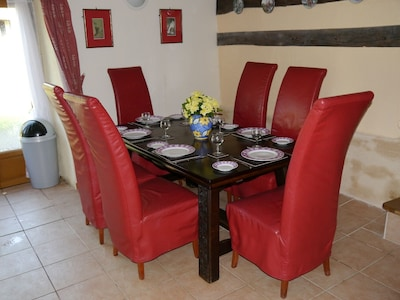 Dining table in kitchen dinner. Set for six, will seat ten with chairs provided.