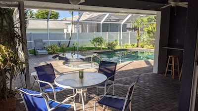 Relax in the covered Lanai with 3 ceiling fans overlooking spa and pool.