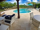 Covered poolside pavilion with comfortable sofa and chairs and dining area.
