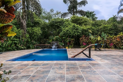 Swimming pool with waterfall and wood-designed railing.