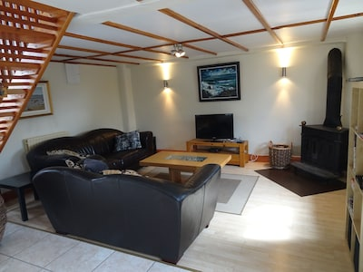 Sitting room open plan with 2 comfortable leather double couches.