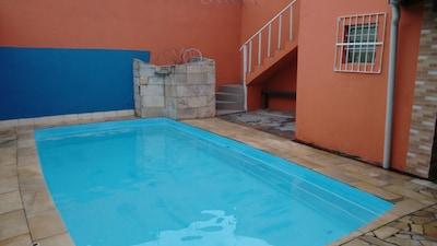 Casa com piscina e salão de jogos, arejada e confortável, pertinho da praia.
