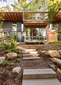 Steps up from the lake lead to this secluded award-winning handcrafted wood home