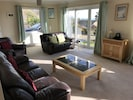 Sunny L-shaped lounge, with french windows to the front and some sea views