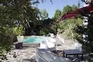 Salon de jardin devant salon et piscine chauffée avec Jacuzzi .