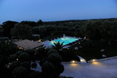 The swimming pool at dusk looking down from the roof terrace