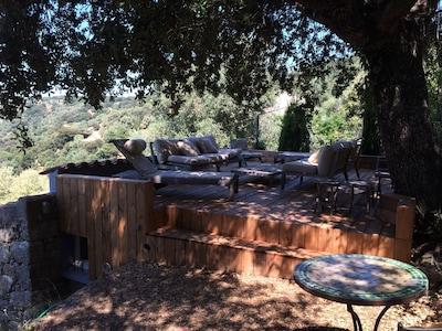 grande terrasse deck sous chêne vert, mobilier teck, vue mer et maquis