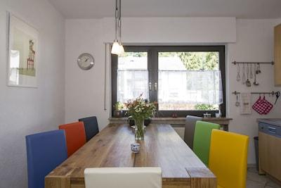 Küche mit großem Esstisch und vielen bunten Stühlen