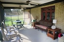 The screened-in porch with plenty of seating and a dining area